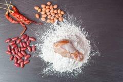 Frisches Ei im Mehl, in den Erdnüssen mit rote Linsen Huhn und im hölzernen Rollen auf schwarzer Tafel Lizenzfreies Stockbild