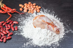 Frisches Ei im Mehl, in den Erdnüssen mit roten Linsen und Huhn und im hölzernen Rollen auf schwarzer Tafel Stockfotos