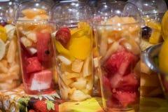 Frisches gehackt und Klumpen trägt in den Plastikschalen früchte, um wegzunehmen verkauft am lokalen Markt stockfoto