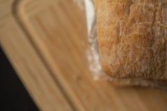 Frisches geschmackvolles panini Sandwich mit Plastiküberschüssiger und Papierpappe nach innen auf hölzernem Brett Aufbereiteter A Stockbilder