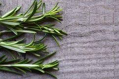 Frisches grünes Rosmarinkraut auf altem hölzernem Hintergrund +EPS Rosemary Ikone Rosemary springen auf einen Holztisch Stockfoto