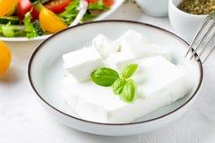 Frisches griechisches Feta in einer Schüssel ganz und Scheiben für Salatesprit lizenzfreies stockbild
