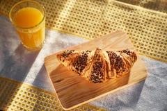Frisches Hörnchen auf einem hölzernen Brett und einem Geschirrtuch mit einer Schale Orangensaft Frisch gebackenes Hörnchen auf ei lizenzfreie stockfotos