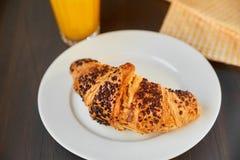 Frisches Hörnchen auf einer keramischen Platte und einem Geschirrtuch mit einer Schale Orangensaft Frisch gebackenes Hörnchen auf stockbilder