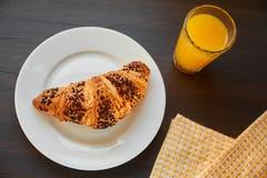 Frisches Hörnchen auf einer keramischen Platte und einem Geschirrtuch mit einer Schale Orangensaft Frisch gebackenes Hörnchen auf stockbild
