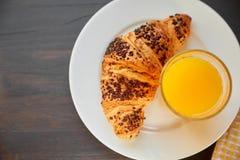 Frisches Hörnchen auf einer keramischen Platte und einem Geschirrtuch mit einer Schale Orangensaft Frisch gebackenes Hörnchen auf lizenzfreie stockfotografie