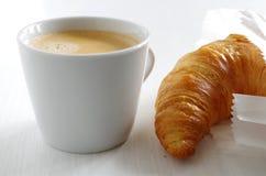 Frisches Hörnchen und Tasse Kaffee lizenzfreie stockfotos