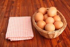 Frisches Huhn eggs im Korb nahe bei Weinlesetischdecke Lizenzfreie Stockbilder