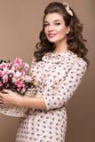 Frisches junges Mädchen, helles Seidenkleid, Lächeln, Retro- Lockenstift-obenart mit Korb von Blumen Schönheitsgesicht, Körper Stockbild