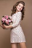 Frisches junges Mädchen, helles Seidenkleid, Lächeln, Retro- Lockenstift-obenart mit Korb von Blumen Schönheitsgesicht, Körper Stockfotos