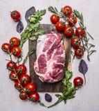 Frisches, köstliches rohes Schweinefleischsteak auf einem Schneidebrett mit Gemüse, Draufsichtabschluß des Hintergrundes der Kräu Stockfotografie