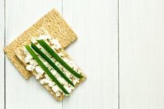Frisches knusperiges Brot mit H?ttenk?se und Fr?hlingszwiebel auf einem wei?en Holztisch Draufsicht, flache Zusammensetzung, Raum stockfoto