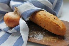 Frisches knusperiges Stangenbrotbrot in einem weißen und blauen Stoff am hölzernen Schreibtisch mit Zwiebel und Seesalz stockfotografie