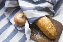 Frisches knusperiges Stangenbrotbrot in einem weißen und blauen Stoff am hölzernen Schreibtisch mit Zwiebel und Seesalz stockfotos