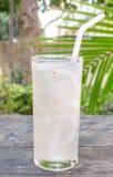 Frisches Kokosnuss-Wasser in einem Glas gesetzt auf einen Holztisch stockfotografie