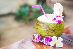 Frisches Kokosnusscocktail verziert mit Orchideenblume und -Sonnenbrille auf einem tropischen Strand Lizenzfreie Stockfotografie