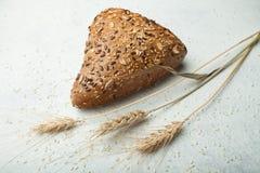 Frisches Mehrkornbrot auf einem weißen Hintergrund, Ohr des Weizens, Gerste stockfotografie