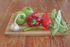 Frisches organisches Gemüse, grüne grüne Bohnen, Knoblauch, grüne Tomate und Pfeffer auf Bretterboden Stockbild