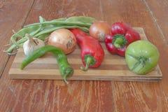 Frisches organisches Gemüse, grüne Tomate, Zwiebel, grüne grüne Bohnen, Knoblauch und Pfeffer auf Bretterboden Lizenzfreies Stockfoto