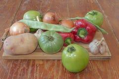 Frisches organisches Gemüse, grüne Tomate, Zwiebel, Kartoffel, grüne grüne Bohnen, Knoblauch und Pfeffer auf Bretterboden Lizenzfreie Stockfotografie