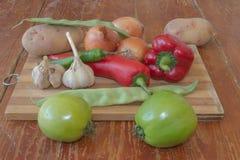 Frisches organisches Gemüse, grüne Tomate, Zwiebel, Kartoffel, grüne grüne Bohnen, Knoblauch und Pfeffer auf Bretterboden Stockfotografie
