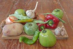 Frisches organisches Gemüse, grüne Tomate, Zwiebel, Kartoffel, grüne grüne Bohnen, Knoblauch und Pfeffer auf Bretterboden Lizenzfreie Stockbilder