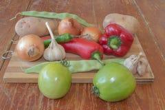 Frisches organisches Gemüse, grüne Tomate, Zwiebel, Kartoffel, grüne grüne Bohnen, Knoblauch und Pfeffer auf Bretterboden Lizenzfreies Stockbild
