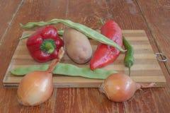 Frisches organisches Gemüse, Kartoffel, Zwiebel, grüne grüne Bohnen, grüne Tomate und Pfeffer auf Bretterboden Lizenzfreies Stockbild