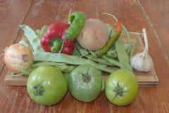 Frisches organisches Gemüse, Kartoffel, Zwiebel, grüne Tomate, grüne grüne Bohnen und Pfeffer auf Bretterboden Stockbild