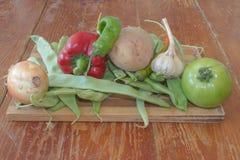 Frisches organisches Gemüse, Kartoffel, Zwiebel, grüne Tomate, grüne grüne Bohnen und Pfeffer auf Bretterboden Lizenzfreie Stockbilder