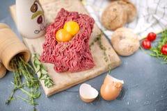 Frisches Rindfleischfleisch im Füllfleisch, auf einem hölzernen Brett Rohe Eier und Tomaten sind klein Kräuter für das Kochen und lizenzfreies stockfoto