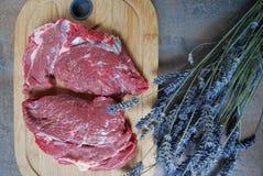 Frisches Rindfleischsteak auf einem Schneidebrett und Lavendel verzweigen sich Stockbild