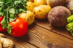 Frisches rohes organisches Gemüse auf einem hölzernen Hintergrund: Tomaten, Kartoffeln, Petersilie, rote Rüben lizenzfreie stockbilder