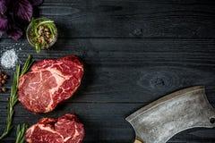 Frisches rohes Rindfleisch mit Basilikum und ein Zweig des Rosmarins mit Axt für Fleisch auf schwarzem hölzernem Hintergrund Besc Stockfoto