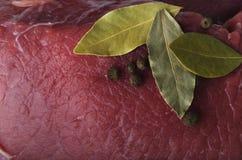 Frisches rohes Rindfleisch mit Lorbeerblättern als Hintergrund stockfotos