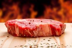 Frisches rohes Rindfleischrippen-Augensteak bereit zum Grill mit Gewürz- und Hintergrundfeuer Stockfotos