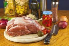 Frisches rohes Schweinefleisch auf einem Schneidebrett mit Gemüse Stockfotos