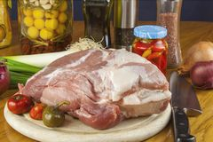 Frisches rohes Schweinefleisch auf einem Schneidebrett mit Gemüse Stockfoto