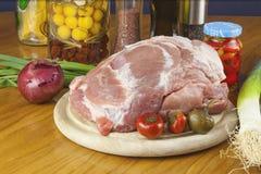 Frisches rohes Schweinefleisch auf einem Schneidebrett mit Gemüse Stockbilder