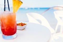 Frisches rotes und orange Cocktail-Glas im Sommer und im Ozean-Hintergrund stockfoto