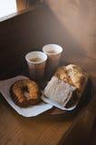 Frisches süßes Bäckereibrot, zwei Kraftpapier-Schalen schwarzer Kaffee auf einem Papierbehälter, hölzerner Hintergrund Mann, der  Lizenzfreies Stockbild