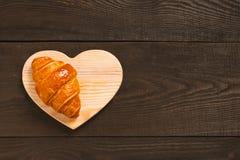 Frisches süßes Hörnchen auf dem braunen Holztisch lizenzfreies stockfoto