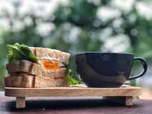 Frisches Sandwich und LattekunstKaffeetasse auf dem hölzernen Behälter Köstliches Frühstück lizenzfreie stockfotografie