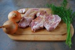 Frisches Schweinefleisch mit Gemüse auf hölzernem Schneidebrett Stockbild