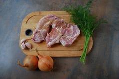 Frisches Schweinefleisch mit Gemüse auf hölzernem Schneidebrett Stockfotografie
