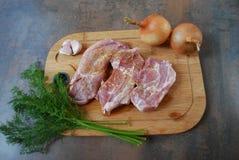 Frisches Schweinefleisch mit Gemüse auf hölzernem Schneidebrett Lizenzfreies Stockfoto