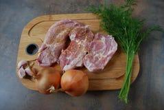 Frisches Schweinefleisch mit Gemüse auf hölzernem Schneidebrett Stockbilder