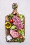 Frisches Schweinefleischsteak mit Salat, Tomate, Öl und Salz auf einem Draufsichtabschluß des Hintergrundes des Schneidebretts hö Lizenzfreies Stockfoto