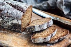 Frisches, selbst gemachtes Brot geschnitten mit Trennmesser auf rustikaler Tabelle, hölzerner Hintergrund stockfotografie