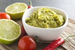 Frisches selbst gemachtes Guacamole mit verschiedenem von den Bestandteilen Schüssel mit mexikanischem Salat auf hölzernem Behält lizenzfreies stockfoto